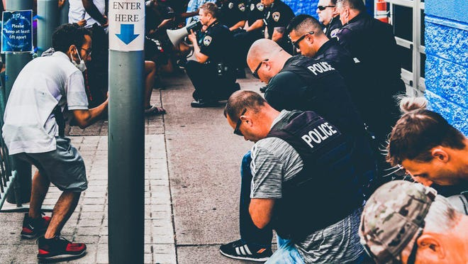 Canton police officers kneel in a moment of reflection and prayer with protesters in downtown Canton on Wednesday when, earlier in the day, an officer resigned before he was terminated for posting racially insensitive and threatening message on social media.