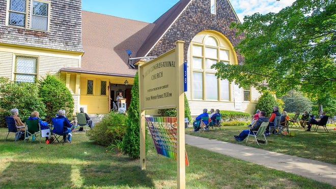 Members and friends of The Little Yellow Church in North Middleboro gather together on the front lawn for worship service.