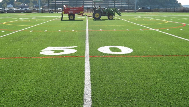 A construction crew puts the finishing touches on Hull High School's new synthetic athletic field last September. Hull's town meeting will be held on the field at 3 p.m.  Saturday, June 13.