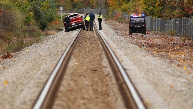 Cohasset police officers walk away from a vehicle that drove onto the Greenbush line train tracks Oct. 25, 2020.
