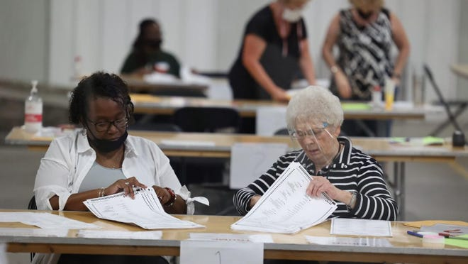 Two workers at the Chatham County Board of Elections begin the hand recount process on Friday.