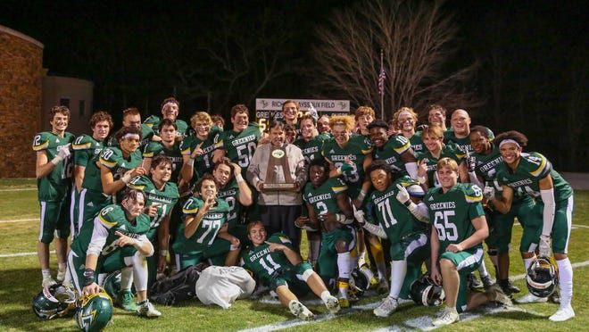 Christ School's football team poses in front of the scoreboard after winning Friday's NCISAA Division II state championship game.
