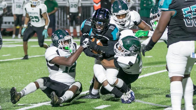 Islands running back Abdul Lara is brought down by Windsor Forest's Demarquez London (No. 12) and Jason Snowdon (No. 14) early in Friday's game at Islands Stadium.