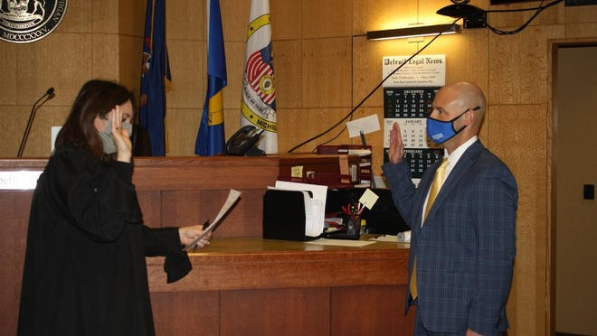 District Court Judge Elizabeth DiSanto from 27th District Court gives the oath of office Jan 13 to Ron Beggs, who was named police chief in the City of Riverview. He leads a force of 25 officers that will patrol 4.5 square miles of the city.
