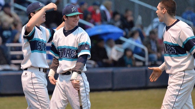 Siegel baseball players (from left) John Ross Dewberry, Jordan Middleton and Blake Benefield after scoring a run in the Stars' 6-2 win over Oakland on Monday to open the season.
