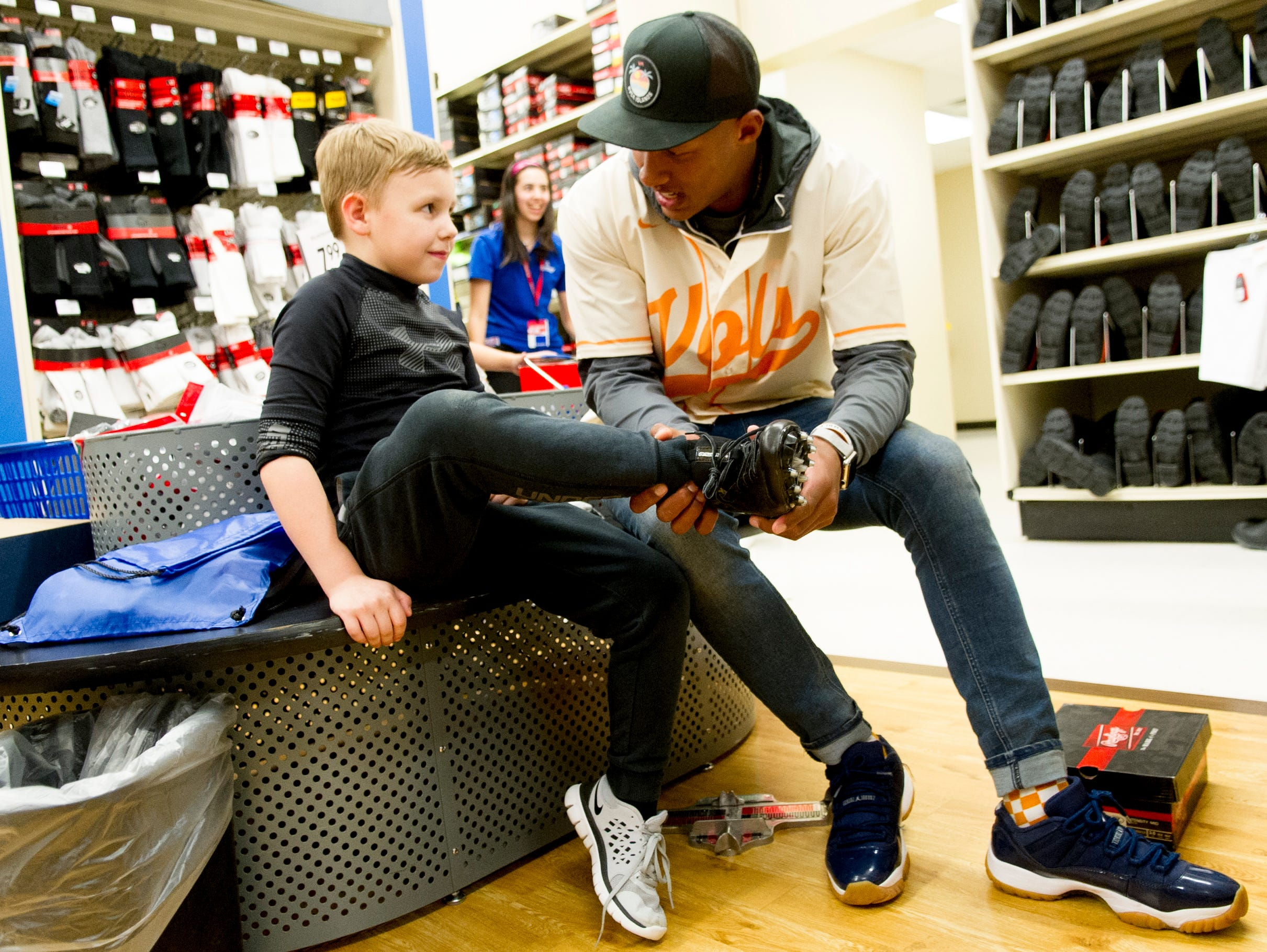 Former UT QB Joshua Dobbs helps Matthew Scott, 8, of Sevierville, with finding football cleats during a football sporting goods shopping spree at Academy Sports + Outdoors in Knoxville, Tennessee on Friday, March 31, 2017. Dobbs held a shopping spree for 11 area kids who are participating in his football camp.