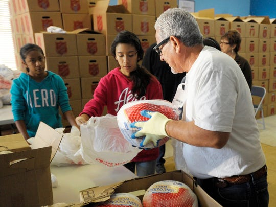 About 500 seniors and low-income families will benefit this Thanksgiving from the food boxes provided by the Visalia Salvation Army, 1501 W. Main St. Above, volunteers Kaylynn Alvarado, 14, left, Fayanne Alvarado, 16, and Ramon Mazon bag turkeys for the food boxes Wednesday. At left, volunteer Rafael Mendoza, 15, helps carry a food box to the car for a woman Wednesday.