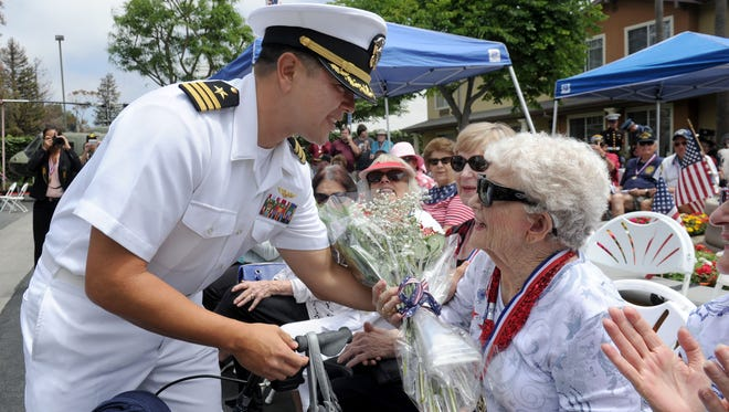 Naval Base Ventura County's operations officer, Cmdr. Mike Posey, presents flowers to Cypress Place Senior Living resident Ginny Caminer, in honor of all relatives of those who have served in the military. This is the 10th year the Ventura retirement community has put on a Salute to Veterans event.