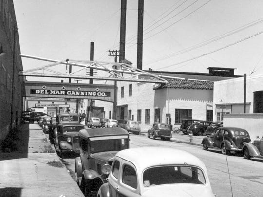 Automobiles line the road along Cannery Row circa 1930.