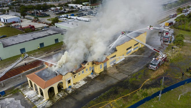 Firefighters spray water on the train depot that caught fire on February 25, 2020 in Delray Beach, Florida.