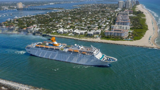 The Grand Celebration cruise ship sails through the Lake Worth Inlet between Palm Beach and Singer Island, Florida, after leaving the Port of Palm Beach to avoid Hurricane Isaias on July 31, 2020.