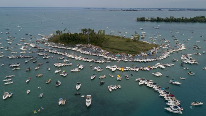 Hundreds of boats congregate around Gull Island, Mich., during the annual Jobbie Nooner in Lake St. Clair, Friday, June 26, 2020. The gathering, an annual celebration of water and sun, is at odds with Michigan's rules intended to curb the spread of the coronavirus.
