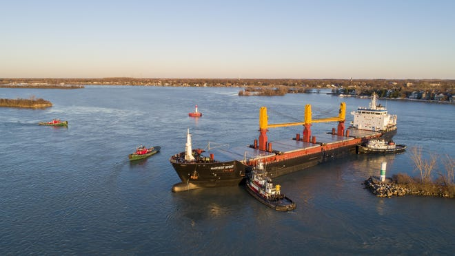 Tugboats work to free the freighter Harvest Spirit that turned sideways and grounded in the Livingstone Channel of the Detroit River between Grosse Ile, Mich., and Bob-Lo Island, Canada, Wednesday Dec. 2, 2020.