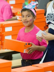 Daniel Pineda smiles while he carries his new pair of shoes  on Tuesday, March 21, 2017, during the Braden Aboud Foundation Shoe Giveaway. Each student received a new pair of Nike sneakers during the event.