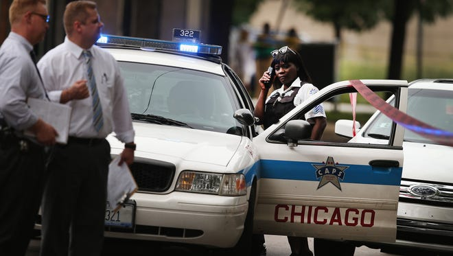 Chicago police investigate the shooting death of 14-year-old Tommy McNeal on Sept. 20, 2013. McNeal was one of at least three killed and about 30 wounded by gunfire in the city within 24 hours.