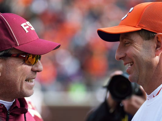Florida State head coach Jimbo Fisher, left, speaks with Clemson head coach Dabo Swinney before an NCAA college football game against Clemson, Saturday, Nov. 11, 2017, in Clemson, S.C. (AP Photo/Rainier Ehrhardt)