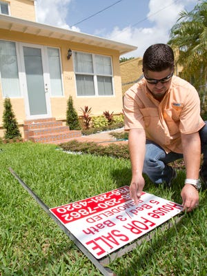File photo taken in April 2015 shows Robert Almirall, director of marketing and special assets coordinator for Mederos & Associates Real Estate, preparing to put up a for-sale sign at a home in Miami's Shenandoah neighborhood.