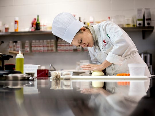 Bethany McKenzie, of Jeddo, concentrates as she prepares vegetables for a dish Friday, Oct. 14, 2016 at the Culinary Institute of Michigan in Port Huron. McKenzie was the top winner at the Michigan Chefs de Cuisine Student Chef of the Year competition. Students at CIM have won the title for three consecutive years.