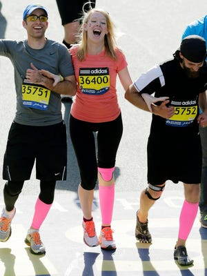 In this April 21, 2014 file photo, Timothy Haslet, left, and David Haslet, right, celebrate with their sister Adrianne Haslet-Davis at the finish line of the 118th Boston Marathon, after she completed a short distance of the course in Boston. Haslet-Davis said she is training to run the entire Boston Marathon on Monday, April 18, 2016. Haslet-Davis lost her left leg below the knee in the April 2013 bombing attacks, which killed three people and wounded more than 260 others.