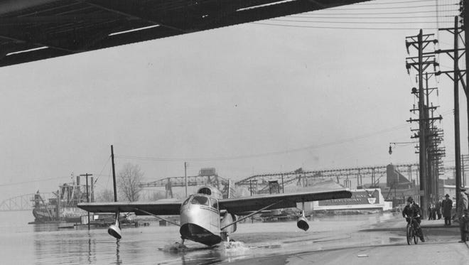 As flood waters rise in February 1950, a seaplane heads underneath the Second Street Bridge across the  Ohio River to reach higher ground.  Feb. 5, 1950.