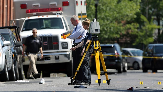 Investigators stand in a street near evidence markers outside the warehouse building where the Art All Night Trenton 2018 festival that was the scene of a shooting that resulted in numerous injuries and at least one death on June 17, 2018, in Trenton, N.J.