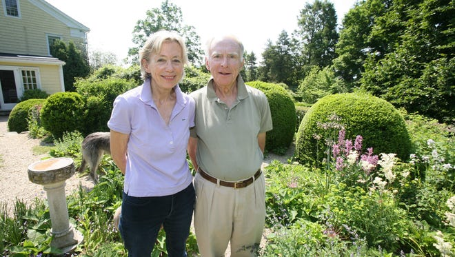 """Page Dickey and her husband Francis """"Bosco"""" Schell stand in the garden at their home for sale in North Salem, June 3, 2014. The 1830 farmhouse includes grounds that cover nearly 3 acres, with pool, husband/pool house, greenhouse, wildflower meadow and many gardens."""