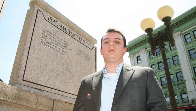 Christopher Arnold, the public affairs director for the Yonkers City Council, is pictured in front of the city's war memorial on South Broadway, June 18, 2014.  Arnold, 32, from Shrub Oak, served as a member of the military in Iraq.
