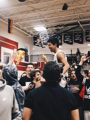 Desert Mountain basketball players and fans celebrate after a victory on Jan. 15, 2016.