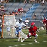 Champlain Valley's Matt Palmer tries to evade South Burlington defender Jeremy Clements in a high school boys lacrosse game Saturday morning. CVU won 10-6.