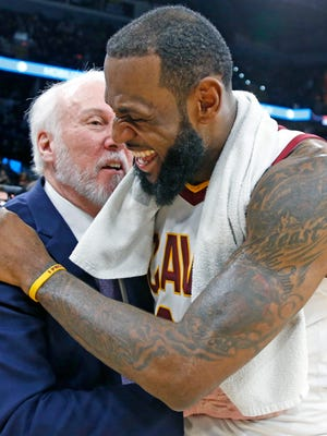 LeBron James of the Cleveland Cavaliers shares a laugh with head coach Gregg Popovich.