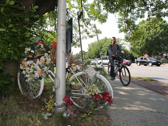 "A cyclist rides past a ""ghost bike"" memorial for Merrill"