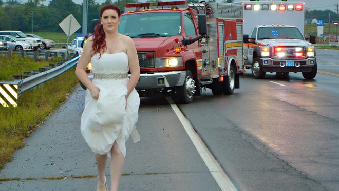 Sarah Ray, a paramedic in her wedding dress, attends to a car crash in Clarksville, Tenn., while en route to her wedding reception.