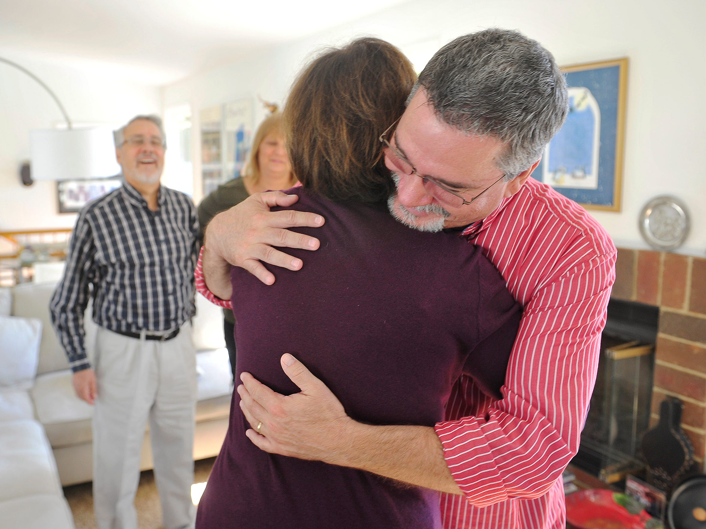 """Odilia """"Odie"""" Caduff hugs Dennis Tingen in her living room as her husband, Rudy Caduff, left, watches."""