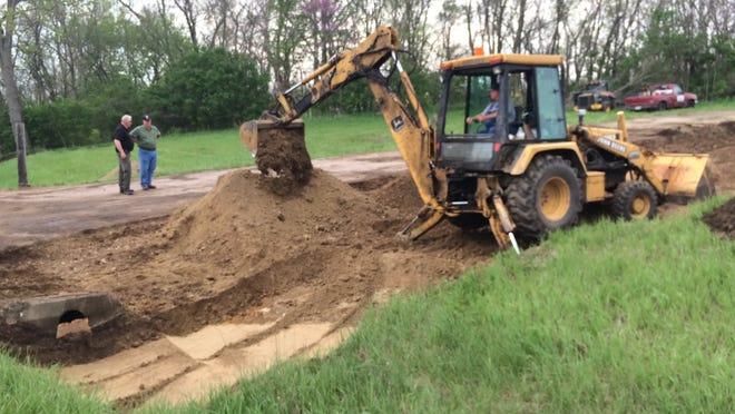 Dirt that was contaminated by a Sunday fertilizer spill is excavated Monday afternoon along Indiana 1 between Cambridge City and Milton.