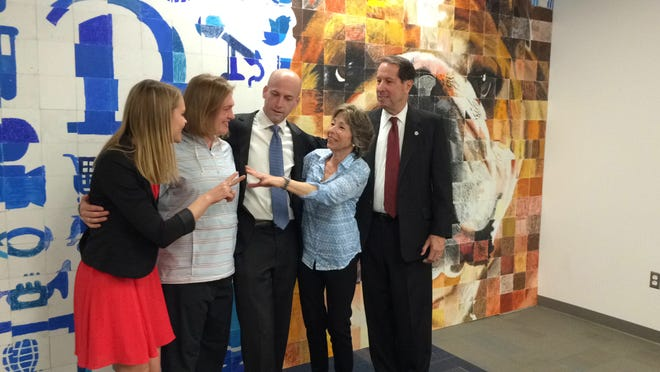 The late Porterhouse's owners Kevin and Erin Bell receive a certificate from Drake University first lady Maddy Maxwell and student leader Elizabeth Bald at a ceremony Friday to dedicate a new mural in Olmsted Hall.