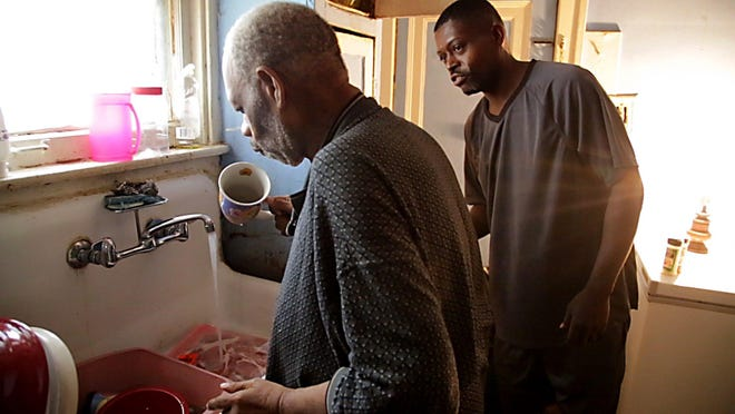 Solomon Bryant, 41, watches as his uncle, Oscar Edwards, 68, puts away his dishes in the kitchen after eating lunch at their family home in Detroit. Bryant moved into the home to help care for Oscar after two other uncles, who were taking care of him, passed away.