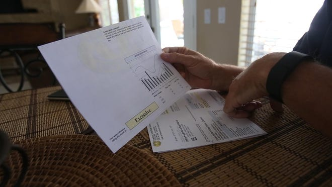 """La Quinta resident Randy Foulds holds an old water bill that labeled his water use """"excessive,"""" next to a newer bill that labels it """"efficient,"""" on July 16, 2015."""