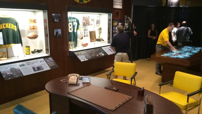 Green Bay Packers Curator Brent Hensel, in yellow, looks at an interactive display in Vince Lombardi's office in the newly revamped Packers Hall of Fame. The museum will re-open to the public on Friday.