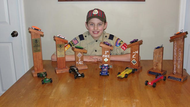 Cub Scout Logan Staskiewicz, 10, of Pack 316 in Brockport shows off his Pinewood Derby cars and trophies from over the years. Logan is a former Pack Champion; this year his car won the Cubmaster's Choice Award.