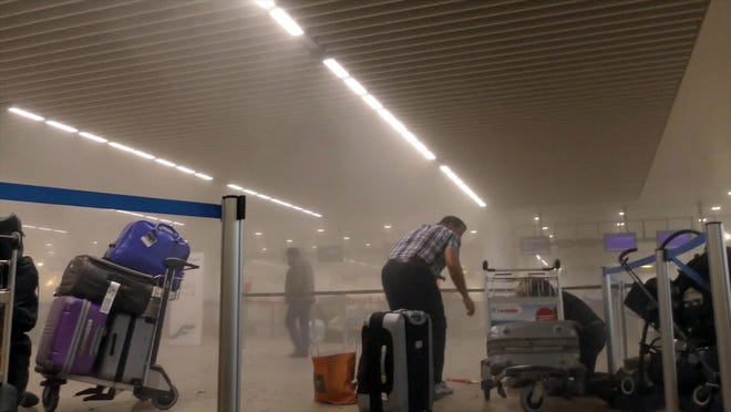 In this photo provided by Ralph Usbeck an unidentified traveller gets to his feet in a smoke filled terminal at Brussels Airport, in Brussels after explosions Tuesday, March 22, 2016. Authorities locked down the Belgian capital on Tuesday after explosions rocked the Brussels airport and subway system, killing a number of people and injuring many more. Belgium raised its terror alert to its highest level, diverting arriving planes and trains and ordering people to stay where they were. Airports across Europe tightened security. (Ralph Usbeck via AP)