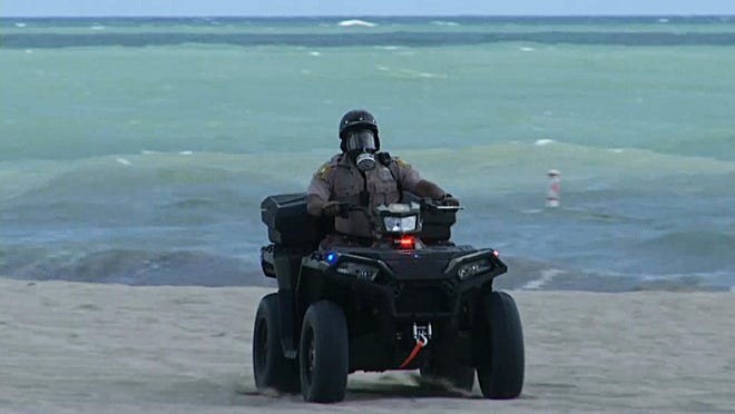 In this image made from video, a Miami-Dade police officer is seen wearing a gas mask and riding an ATV in Miami Beach during a red tide outbreak in 2018.