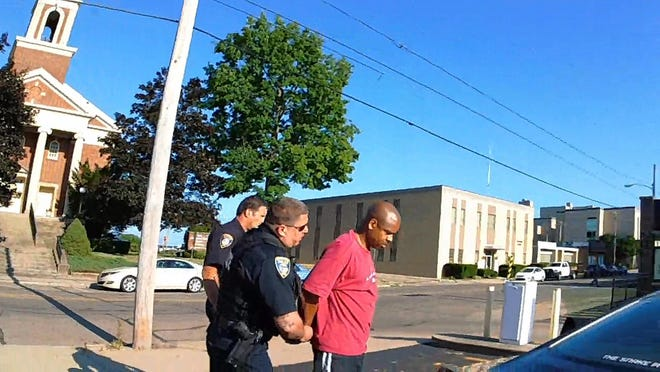 Darren Cooper, right, is detained Aug. 13 in front of the Portage County Job and Family Services building by two Ravenna police officers after a caller falsely reported he had a gun. It was a cellphone.