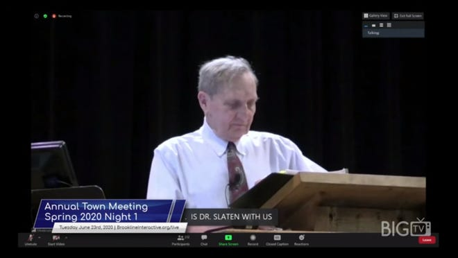 Brookline's Town Meeting Moderator Sandy Gadsby, alone at the podium while TM members Zoom into the meeting from home.