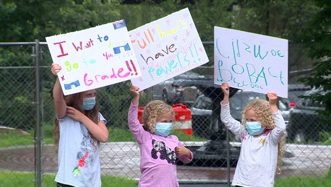 A group of children stood outside the State House Wednesday, Aug. 12 holding signs as parents rallied for an in-person education in the fall. WCVB photo