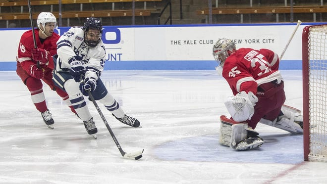 Yale's Luke Stevens tries to keep control of the puck during a preseason scrimmage against McGill University.
