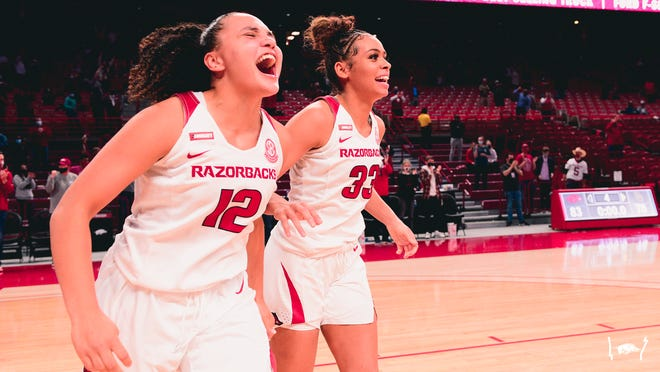 Arkansas guards Destiny Slocum (12) and Chelsea Dungee (33) celebrate after upsetting No. 4 Baylor on Sunday at Bud Walton Arena in Fayetteville.
