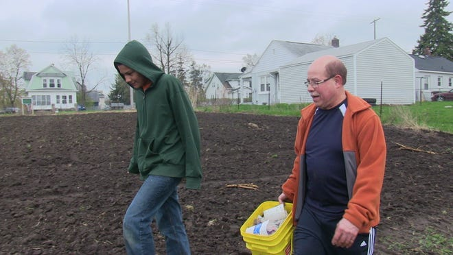 Marcos Rice, left, and James Moreno clean up the Post-Franklin Community Garden Saturday before spring planting can be done.