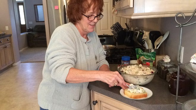 """Rosemary """"Rosi"""" Pazurek spreads some homemade chicken salad on a thick slice of homemade bread."""