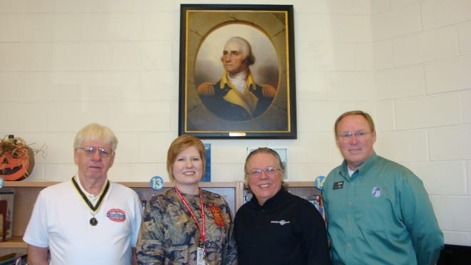Jerry Montgomery, Arkansas Society, Sons of the American Revolution state president (from left), Leah Cotter, Nelson-Wilks-Herron Elementary School principal; Joe Miles, Integrity First Bank president and John Reding, Integrity First Bank Business Development/Marketing vice president are shown at the presentation of a framed replica Rembrandt Peale portrait of General George Washington in the school's library. The portrait was made available from the Mount Vernon Ladies Association through the SAR with a grant from Integrity First Bank.