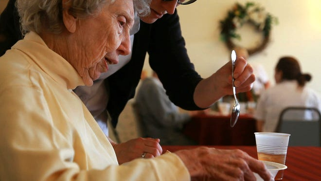An aide at Blue Ridge Christian Home in Raphine guides resident Louise Ramsey during lunch. Prompting and cues enable Ramsey, who lives with dementia, to feed herself, instead of being fed by others.
